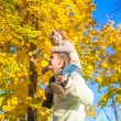 Little girl with happy father having fun in autumn park on a sunny day — Stock Photo