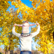 Stock Photo: Little girl riding on father's shoulders in autumn park
