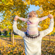 Back view of Little girl riding on father's shoulders in autumn park — Stock Photo