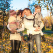 Family of four walk in autumn park on a sunny warm day — Stock Photo #34012211
