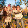 Family of four with two kids having fun in autumn park on a sunny warm day — Stock Photo
