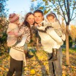 Family of four having fun in autumn park on a sunny warm day — ストック写真