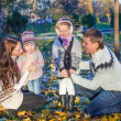 Young beautiful family of four enjoyed relaxing in autumn park — Stock Photo