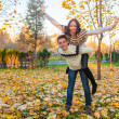 Happy family of two having fun in autumn park on a sunny fall day — ストック写真