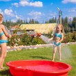 Two little sisters frolicing, splashing and having fun in their yard — Stockfoto