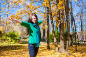 Happy young woman having fun her autumn vacation in park — Stock Photo