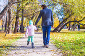Rear view of young father and little girl walking in autumn park — Stock Photo