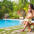 Stock Photo: Young mother and her little daughter near swimming pool