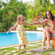 Stock Photo: Young mother and her little daughter have fun near swimming pool