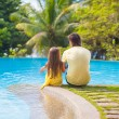 Rear view of a young father and his cute daughter sitting by the swimming pool — Stock Photo #35211239