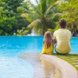 Rear view of a young father and his cute daughter sitting by the swimming pool — Stock Photo #35211265
