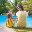 Back view of young father and his cute daughter sitting by the swimming pool — Stock Photo #35211283