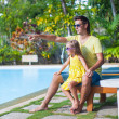 Little girl with her father have fun near the swimming pool at exotic resort — Stock Photo
