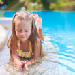 Closeup of Cute little girl in the swimming pool looks at camera — Stock Photo #35211537