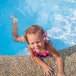 Little cute girl with flower behind her ear in the swimming pool — Stock Photo