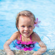 Little cute girl with flower behind her ear in the swimming pool — Stock Photo #35211737