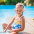 Adorable girl with flower behind her ear sits near swimming pool — Stock Photo