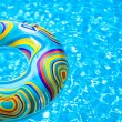 Inflatable colorful Rubber Ring floating in blue swimming pool — Stock Photo #35211953