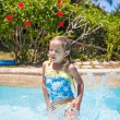 Little girl jumping and having fun in swimming pool — Stock fotografie