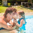 Little cute girl play with father at the pool in tropical hotel — Stock Photo