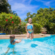 Little girls jumping and having fun in swimming pool — Stock Photo