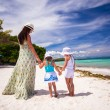 Rear view of two girls and their mother on a white, tropical beach — Stock Photo