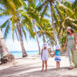 Mother walking with her two kids along a tropical beach — Stock Photo