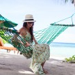 Happy young woman relaxing in the hammock on tropical beach — Stockfoto
