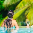 Back view of young beautiful woman enjoying the luxury quiet swimmingpool — Stock Photo