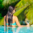 Rear view of young beautiful woman enjoying the luxury quiet swimmingpool — Stock Photo