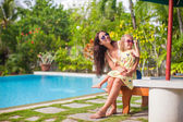 Mother and little daughter relax near swimming pool — Stock Photo