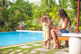 Young mother and her little daughter have fun near the swimming pool — Stock Photo