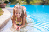 Closeup of Cute little girl in the swimming pool looks at camera — Stock Photo