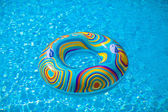 Colorful pool float in blue swimming basin — Stock Photo