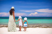 Rear view of fashion young mother and two her kids at exotic beach on sunny day — Stock Photo
