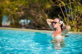 Hermosa joven disfrutando de la piscina tranquila de lujo — Foto de Stock