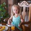 Stock Photo: Adorable little girl having breakfast and drinking fruit cocktail