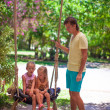 Stock Photo: Dad shakes his young daughters on swing in tropical hotel