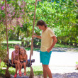 Dad shakes his young daughters on a swing in tropical hotel — Stock Photo