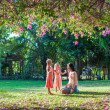 Stock Photo: Young mother with her little daughters sitting in lush garden and enjoy summer rest