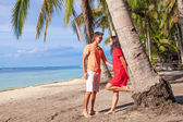 Romantic couple at tropical beach near palm tree — Stock Photo