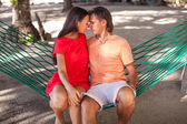 Portrait of Young loving couple in a hammock at white sand beach — Stock Photo