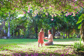 Little girl with mother sitting in the lush garden and enjoy summer rest — Stock Photo