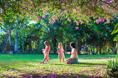 Young mother with her little daughters sitting in the lush garden and enjoy summer rest — Stock Photo