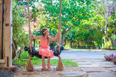 Beautiful little girl swinging on a swing in cozy flowered courtyard — Stock Photo