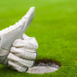 Men's hand in a glove golf shows OK near the hole — Stock Photo