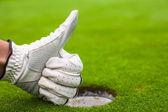 Mano de los hombres en un campo de golf de guante muestra bien cerca del agujero — Foto de Stock
