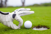 Close-up of a man's hand putting golf ball in hole at course — Stock Photo