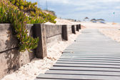 Vista cercana de un tablero de madera caminar en la playa — Foto de Stock