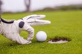 Primer plano de la mano de un hombre poniendo la pelota de golf en el agujero en el curso — Foto de Stock